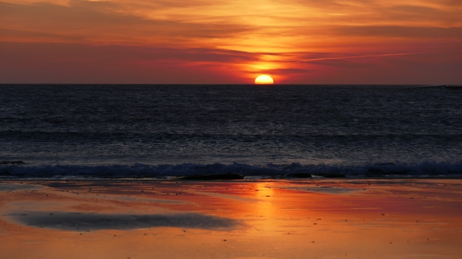 Sun setting into the sea, reflected in water on the beach.